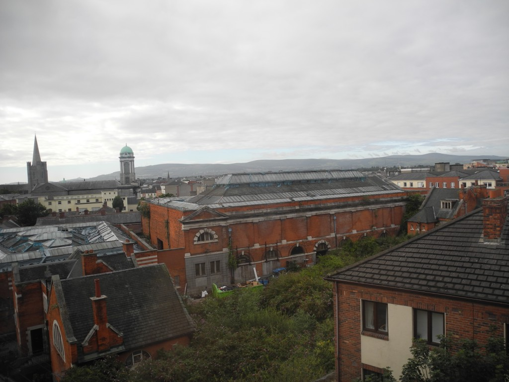Blick aus dem Fenster: verlassene Industrieanlagen und in der Ferne die Berge
